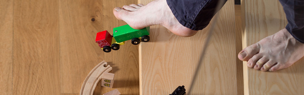 A man getting ready to slip and fall on a toy train has accident insurance.