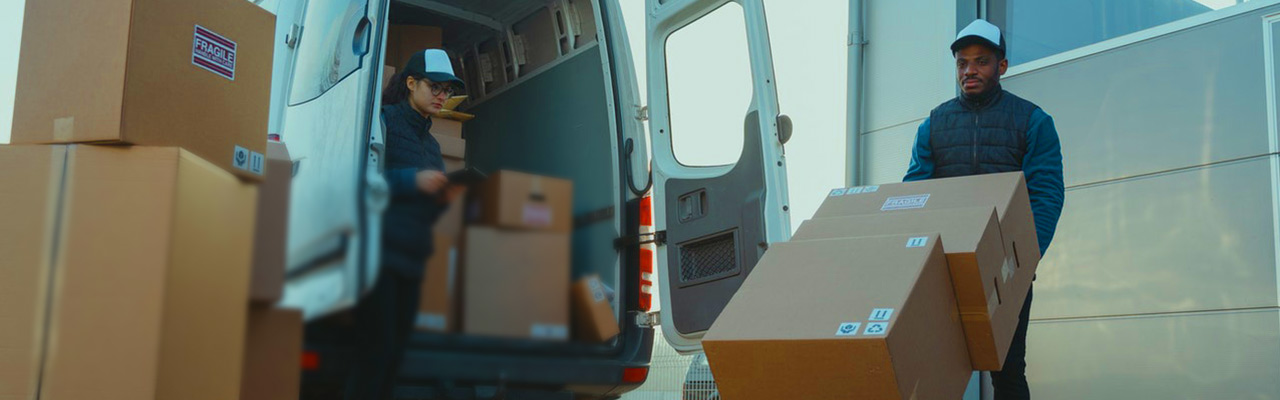 Employees unloading boxes of merchandise from a cargo van.